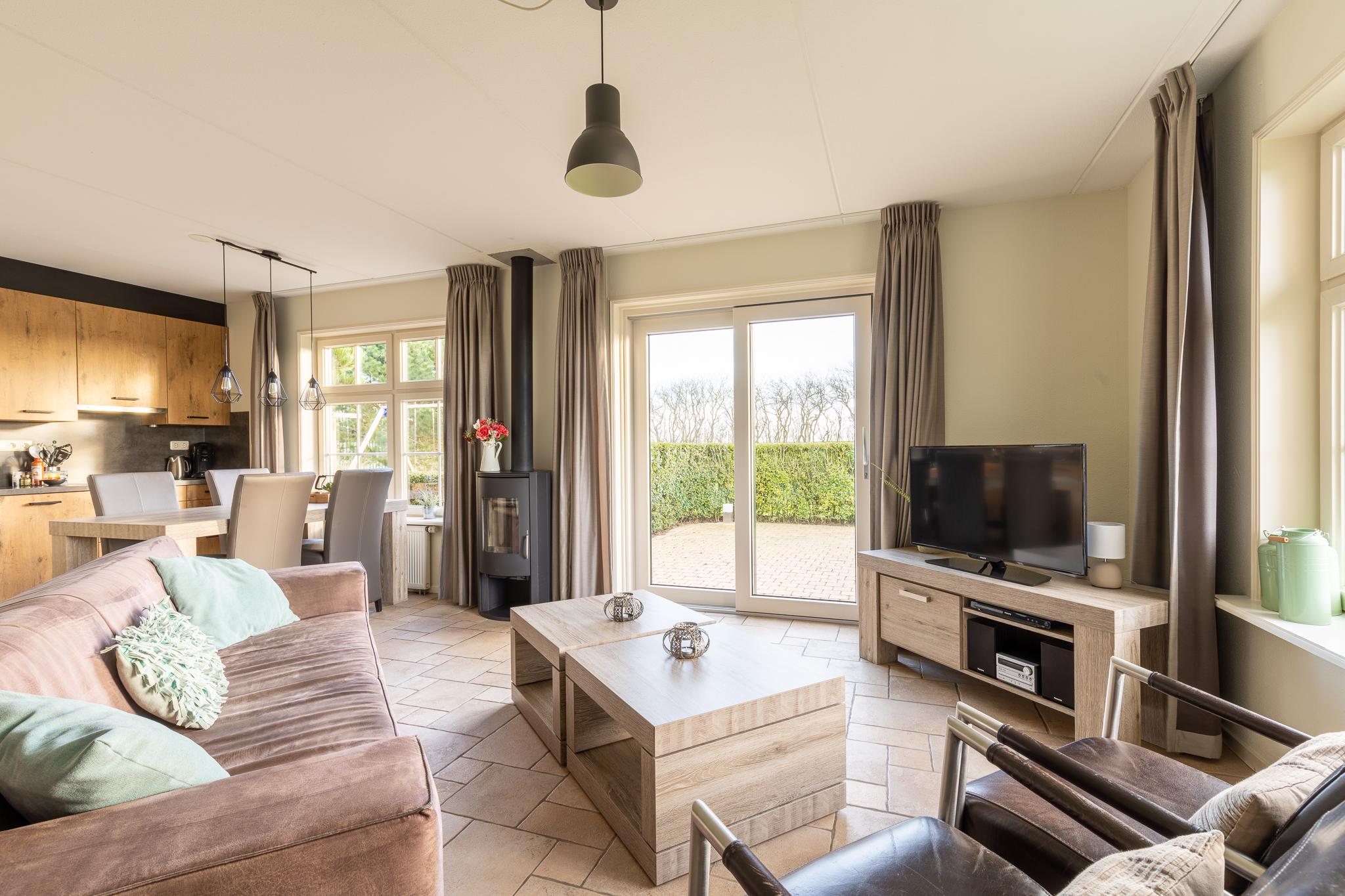 Sfeervolle woonkamer met houtkachel en schuifdeur naar het terras